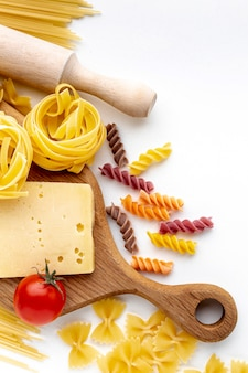 Flat lay mix of uncooked pasta with tomatoes and hard cheese