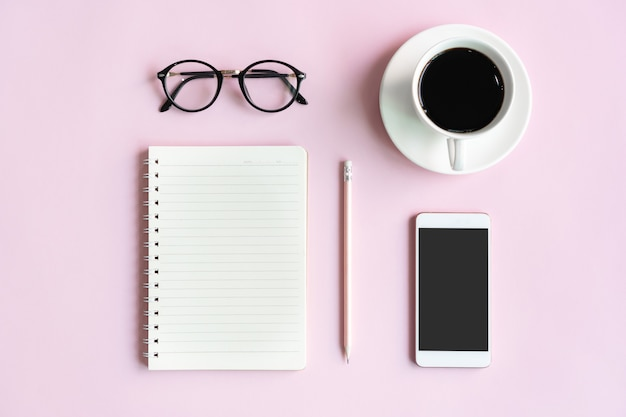 Flat lay of mobile phone, a cup of coffee, glasses and notepad of businesswoman on pink table in office. business and technology concept top view and copy space.