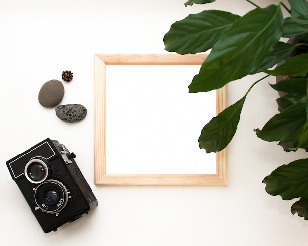 Flat lay mock up, top view, wooden frame, old camera, plant and stones.