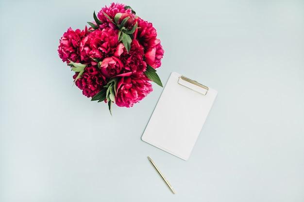 パステルブルーの表面にクリップボードとピンクの牡丹の花の花束でフラットレイモックアップ