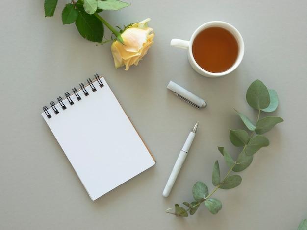 Плоский макет стола блогера с эвкалиптом, блокнотом, пустой страницей и чашкой чая. копировать пространство