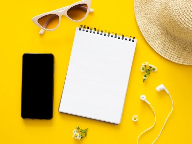空白のノートブック、スマートフォンの画面、イヤホン、コピー領域の背景を持つ麦わら帽子とフラットレイアウトのモックアップデスク。モバイルアプリ、サイトのスクリーンショットのアイデア。