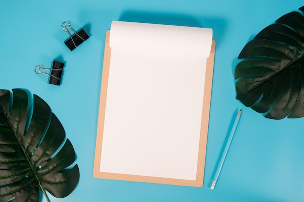 Flat lay mockup paper a4 with clipboard, palm leaves and pencil on blue background.