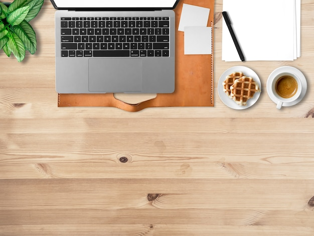 Flat lay of modern laptop workspace office of freelance with coffee waffles and document papers.