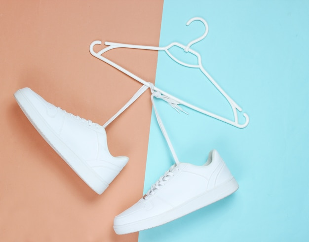 Flat lay of modern white sneakers  shoes with hanger on pastel background.