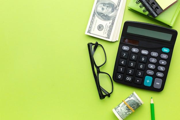 Disposizione piatta di denaro e calcolatrice