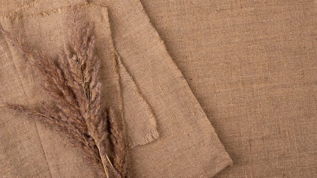 Flat lay of monochromatic selection of textiles with copy space and dried grass