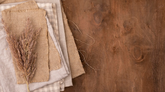 Flat lay of monochromatic selection of textiles with dried grass and copy space