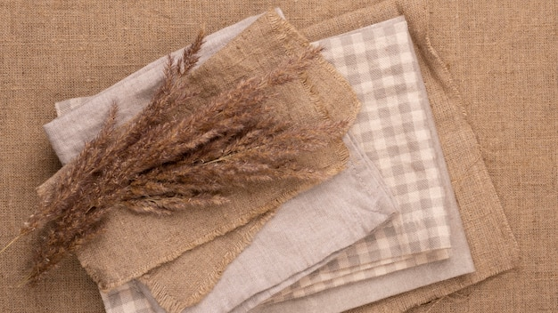 Flat lay of monochromatic selection of textiles with dried grass