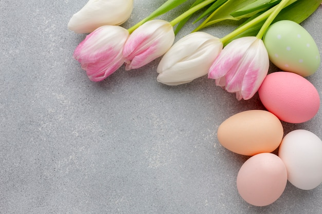 Flat lay of multicolored easter eggs and tulips