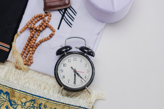 Flat lay of muslim dressed and accessories for salat with prayer beads and clock showing fajr time pray