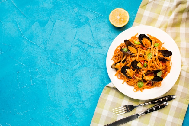 Flat-lay mussel pasta on tablecloth with copyspace