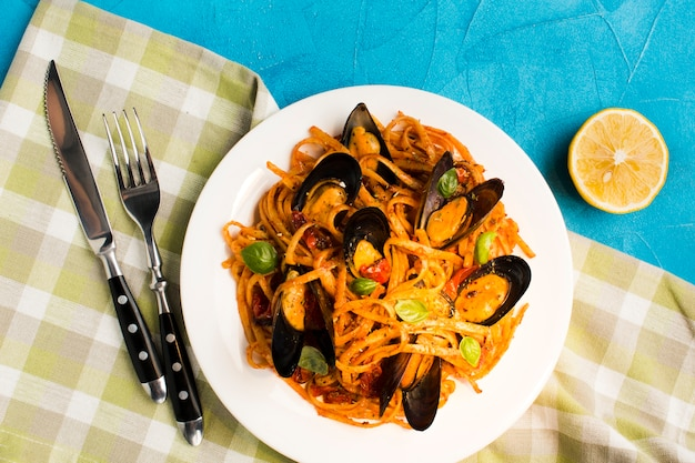 Flat-lay mussel pasta on tablecloth