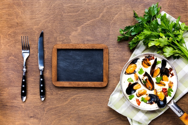 黒板とテーブルクロスの上のホワイトソースのムラサキイガイ