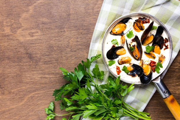 Flat-lay mussels in white sauce and parsley on tablecloth with copyspace