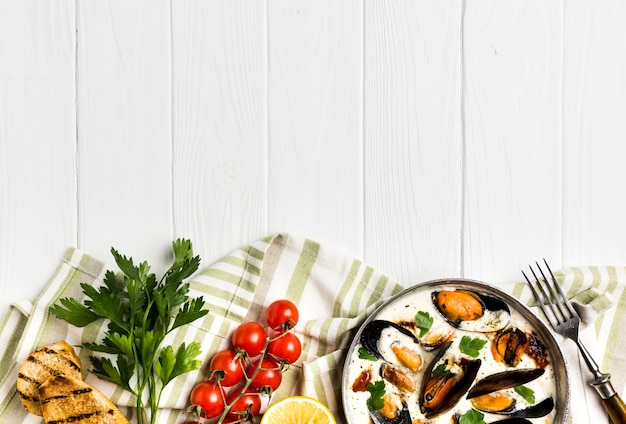 Flat-lay mussels in white sauce and sides on tablecloth with copyspace