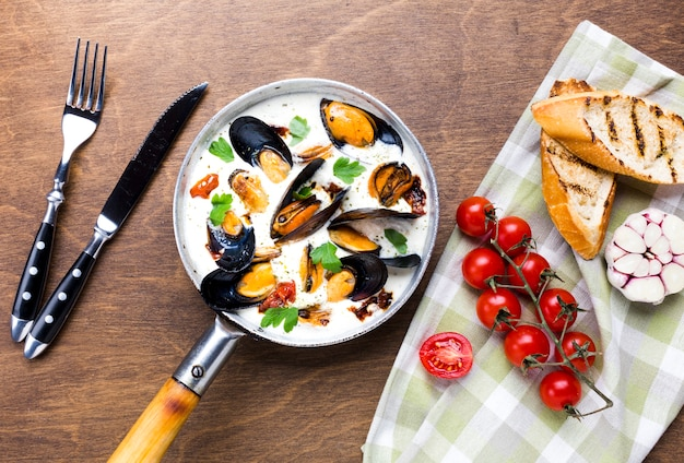 Flat-lay mussels in white sauce and sides on tablecloth