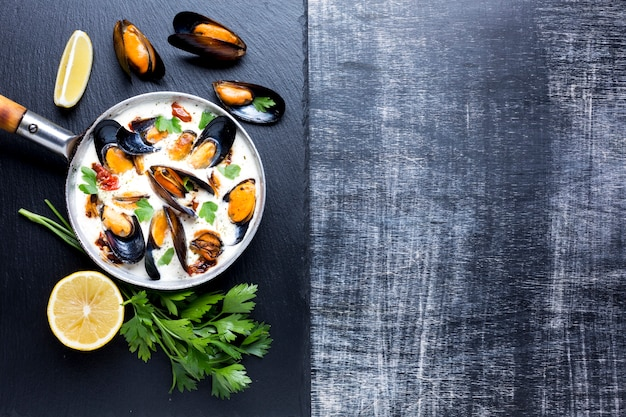 Flat-lay mussels in white sauce on slate with copyspace