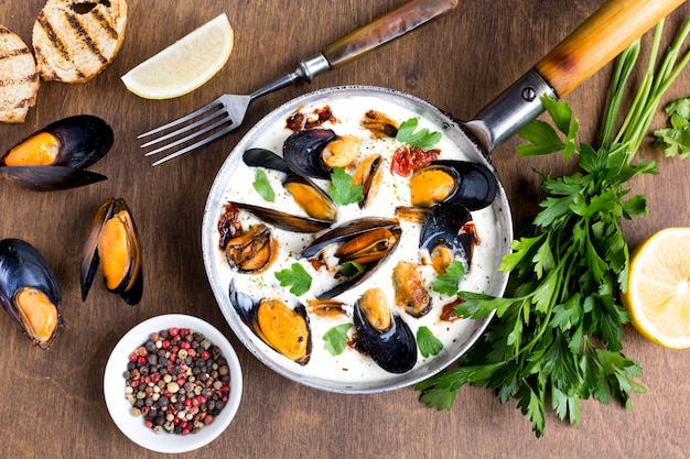 Flat-lay mussels in white sauce and spices