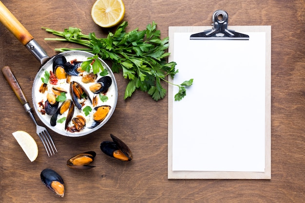 Flat-lay mussels in white sauce on tablecloth with clipboard