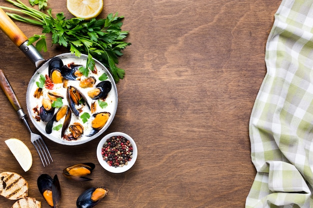Flat-lay mussels in white sauce and tablecloth with copyspace