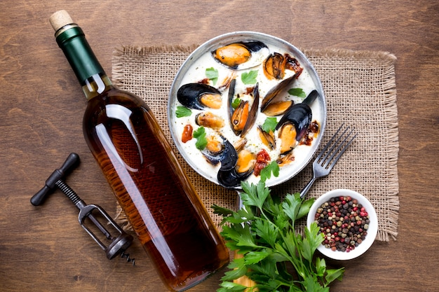 Flat-lay mussels in white sauce and wine bottle