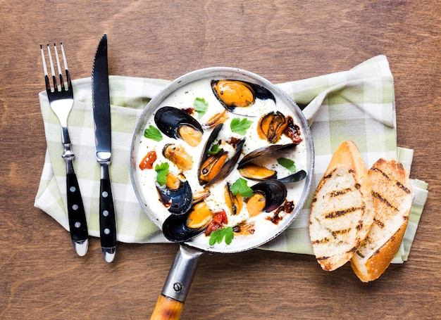 Flat-lay mussels in white sauce with cutlery on tablecloth