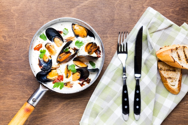 Flat-lay mussels in white sauce with tablecloth and cutlery