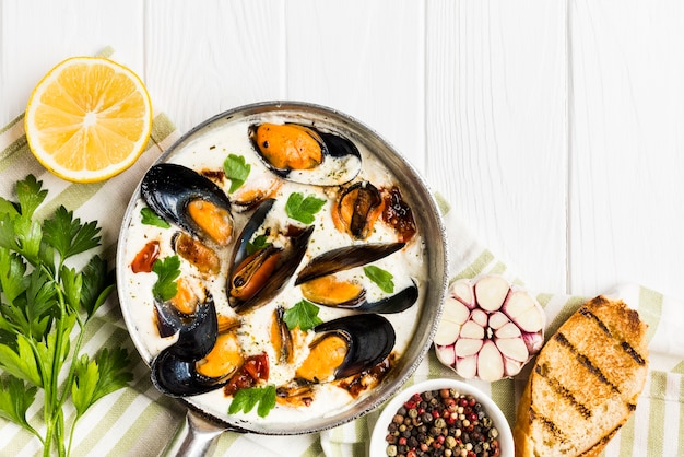 Flat-lay mussels in white and wine sauce on tablecloth with sides