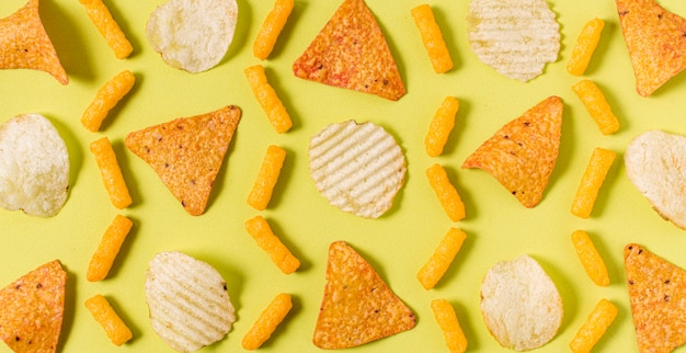 Flat lay of nacho chips with potato chips and cheesy puffs