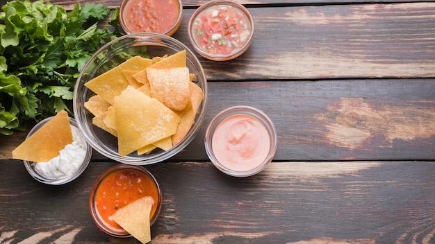 Flat lay of nachos, salad and sauces