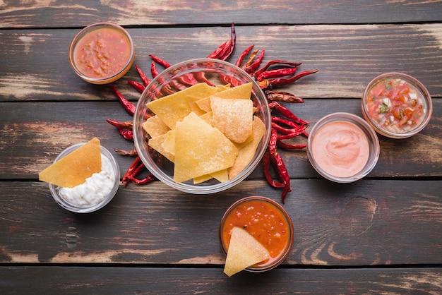 Flat lay of nachos with chili peppers and dip sauces