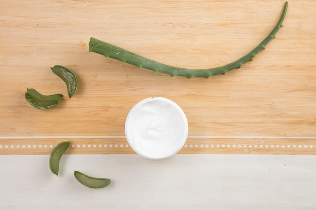 Flat lay of natural body cream and aloe vera
