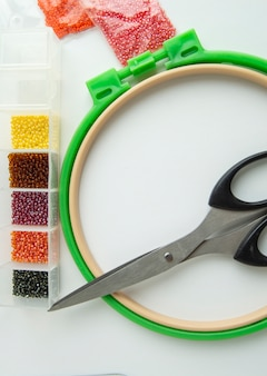 Flat lay needlework and embroidery accessories, scissors hoops and beads