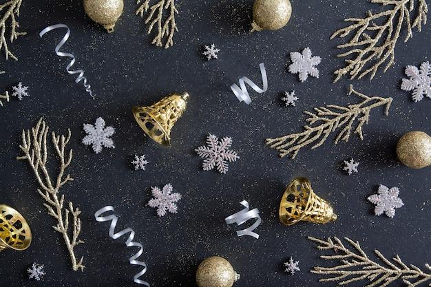 ハッピークリスマスの花輪、雪片、金色の鐘で飾られたフラットレイ新年クリスマス黒の背景パターン