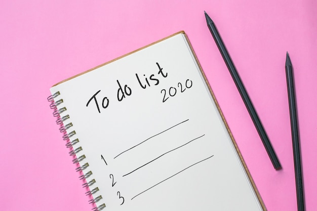 Flat lay new year to do list on blank notebook, planning wish 2020 concept