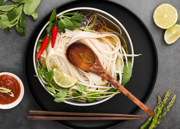 Flat lay of noodles in bowl with spoon and sauce