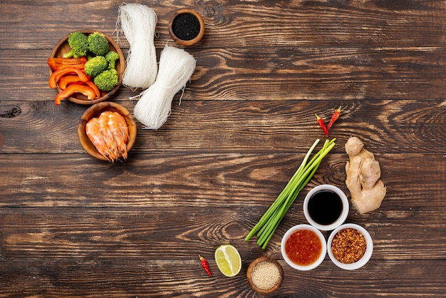 Flat lay noodles spices and chopsticks on wooden backgrouns