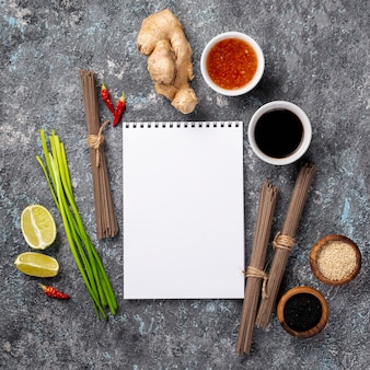Flat lay noodles and spices with blank notebook