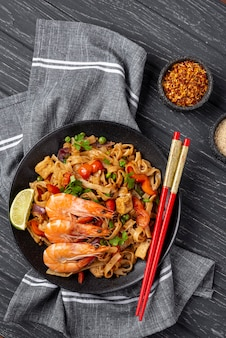 Flat lay noodles with vegetables and chicken with chopsticks and spices