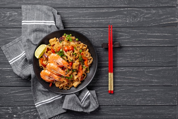 Flat lay noodles with vegetables and chicken with chopsticks