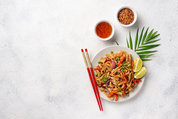 Flat lay noodles with vegetables chopsticks and spices with copy space