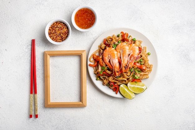 Flat lay noodles with vegetables and shrimp chopsticks and spices with wooden frame
