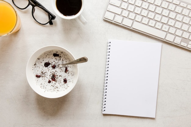 Flat lay notebook and bowl with yogurt raisins and chia seeds