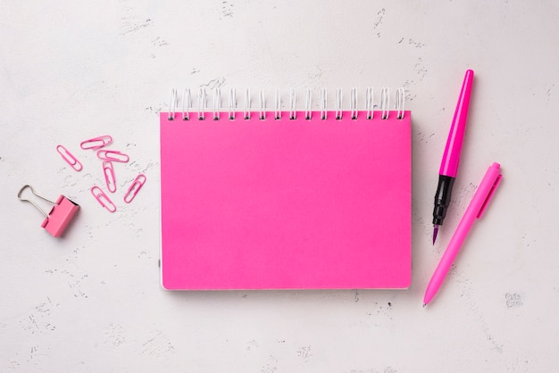 Flat lay of notebook on desk with pen and paper clips