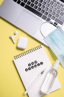 Lay piatto del notebook accanto alla mascherina medica con disinfettante per le mani
