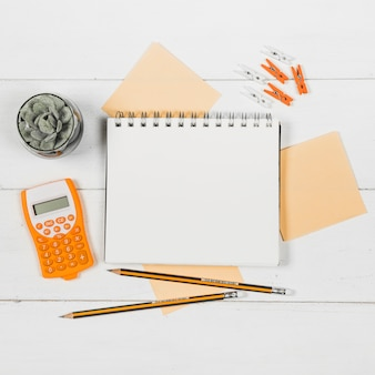 Flat lay of notebook mock-up surrounded by orange supplies