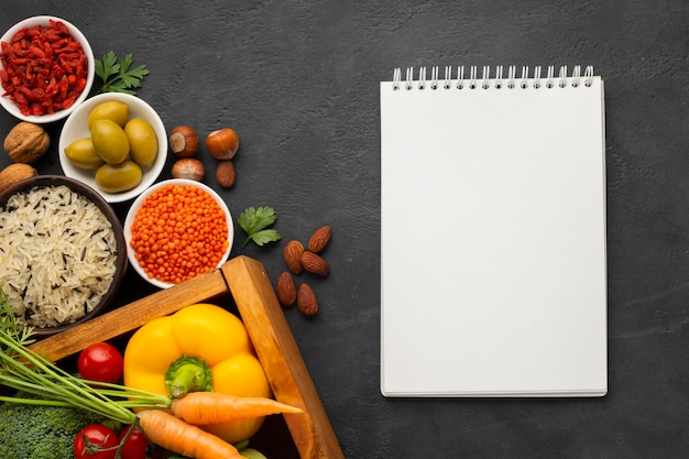Flat lay of notebook mock-up and vegetables
