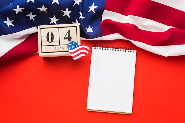 Flat lay of notebook with american flag and date