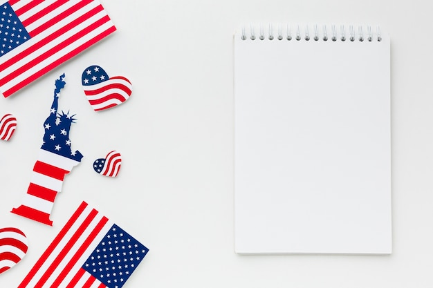 Flat lay of notebook with american flags and statue of liberty